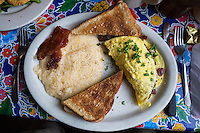 New Orleans, Louisiana.  Bacon and Sausage Omelet, Praline Bacon, Toast, and Grits, Breakfast at Elizabeth's Restaurant, Bywater District.