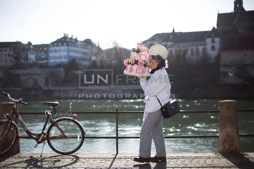 A masked participant in the Carnival of Basel, or Fasnacht, carries a cake along the banks of the Reine River in Basel, Switzerland on the final day of festivities. Feb. 25, 2015.