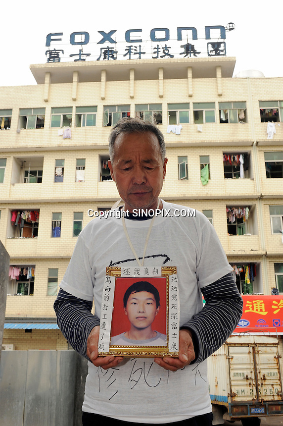"Ma Zishan, 58, holds a portrait of their dead son Ma Xiangqian, 18, who died after ""falling from a great height"" from a Foxconn dormitory 23rd Jan 2010 .  The family believe that foul play was involved. Ma Xiangqian had been forced to clean toilets for a month before he died. <br />