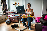 A young graphic designer breastfeeds her baby whilst working at her computer at home.<br /> <br /> 10/09/12<br /> Berkshire, England, UK