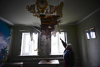A citizen of Slovyansk shows the ceiling of her house heavily damaged by shelling during ceasefire.