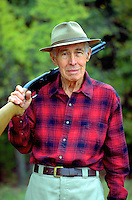 portrait of senior citizen who is hunting in a relaxed pose with gun in the outdoors. Ray. United States outdoors.