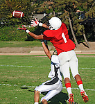 Football action. Wide receiver goes up to take the ball.