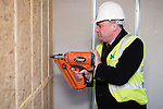 © Joel Goodman - 07973 332324 .  04/02/2014 . Manchester , UK . ED BALLS tries the nail gun . Ed Balls , MP for Morley and Outwood and Shadow Chancellor of the Exchequer the Labour Party , joins Labour candidate Mike Kane on the campaign trail ahead of the Wythenshawe and Sale East by-election , following the death of MP Paul Goggins . They visit apprentices at the Leybrook Road building site in Wythenshawe where apprentice builders work on bungalows built for affordable rent . Photo credit : Joel Goodman