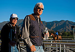 Bob Baffert walks to his spot in the grandstand to watch a set of his horses exercise during Breeders' Cup week. Baffert walks with Bernie Schiappa, part owner of Game On Dude.