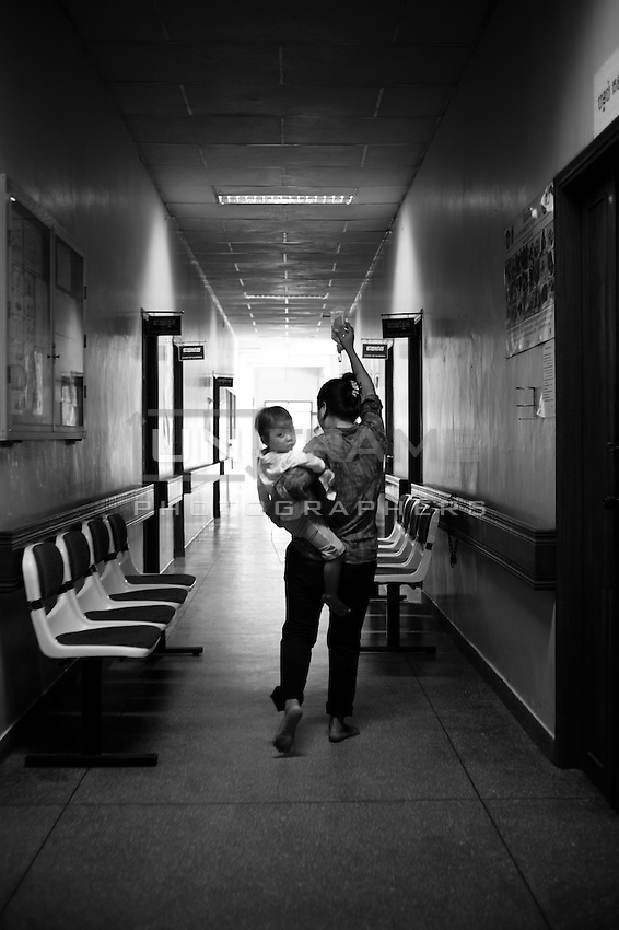 A young mother walking barefoot down the hospital corridor. Holding her child in one hand and using the other to hold a drip flask.
