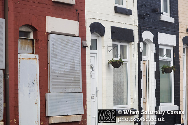 Hanging baskets on occupied houses next to a derelict property on Walton Breck Road, Liverpool, one of the streets which has been earmarked for regeneration by the Anfield and Breckfield Housing & Physical Regeneration Group, but which is now in doubt due to funding being cut. Photo by Colin McPherson.