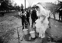 En tjsetsjensk brud henter vann fra en utendørs kran, som hun sa? skal bære inn i huset til sine svigerforeldre. Dette er en tjsetsjensk tradisjon som skal symbolisere livet....