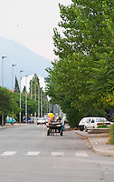 One of the main roads leading in to Podgorica, A horse drawn cart on the street. Podgorica capital. Montenegro, Balkan, Europe.