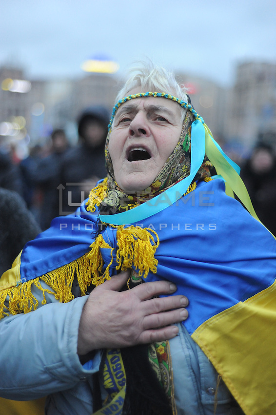 Elder Ukrainian woman singing national anthem. People gather in the Independence square in Kiev. Ukriane in the night of EU summit in Vilnus. Thousands of people are continuing to express their support to european integration and protesting against decision of Ukrainian government to refuse signing of association with EU in Vilnius.