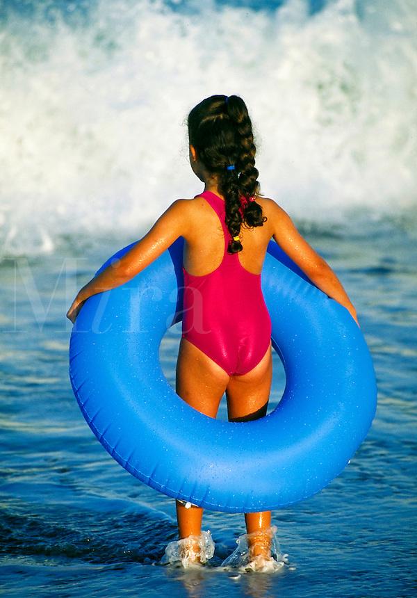 Girl with beach tube watching the waves break, Nauset Beach, Orleans, Cape Cod, MA