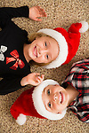 Brother (6-7) and sister (6-7) in Santa hats lying on carpet