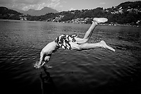 Switzerland. Canton Ticino. Agno. The diver in Lake Lugano. A young man jumps and dives into the water. Lake Lugano (or Ceresio Lake) is a glacial lake. 29.06.2020 © 2020 Didier Ruef