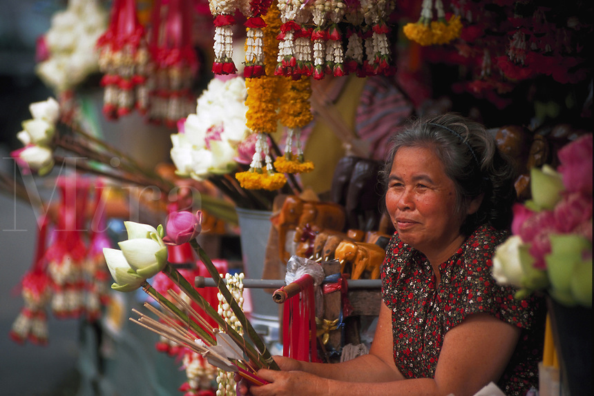 Woman selling flowers and incense for believers to use at roadside Buddhist shrine, Chaing Mai, Thailand