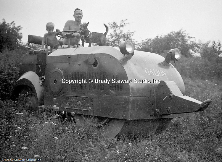 Mt. Washington:  View of Father, Son, and dog sitting on road paving equipment used during the construction of Chatham Village in Pittsburgh.  This was a gas-driven roller but if it ran out of gas, it could be pulled by another vehicle (see front hook).