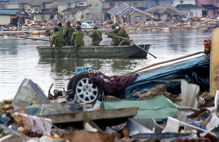 Japanese Self  Defence Force soldiers look for bodies in the water that has flooded and engulfed Natori near Sendai, Japan. The earthquake, tsunami and nuclear fallout has meant that the March 11th quake was the most expensive natural disaster known to man..16 Mar 2011.