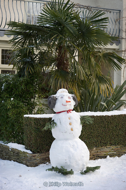 Snowmman and palm tree in a suburban street, London.