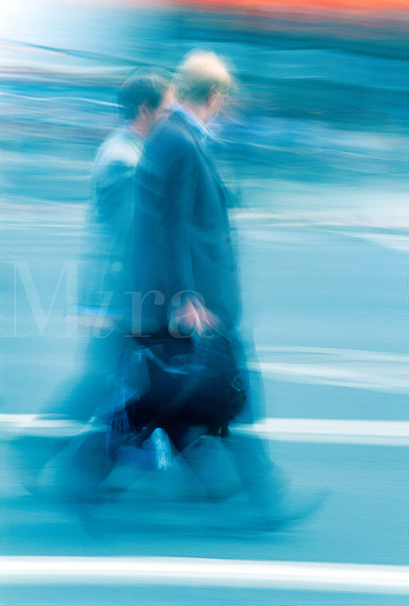 Blurred shot of business men walking in a busy downtown setting