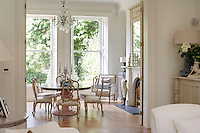 An elegant dining room has a Moissonnier central pod dining table and Massant calico-covered dining chairs in an antiqued grey finish. Uncurtained windows allow plenty of light into the room.
