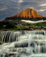 Reynolds Creek with Spring waterfall on Creek at sunset. Glacier National Park, Montanna