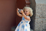 Cute little blond girl focuses her subject through the viewfinder of her camera.