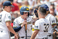 Michigan Wolverines shortstop Jack Blomgren (2) is greeted by his teammates after scoring during Game 11 of the NCAA College World Series against the Texas Tech Red Raiders on June 21, 2019 at TD Ameritrade Park in Omaha, Nebraska. Michigan defeated Texas Tech 15-3 and is headed to the CWS Finals. (Andrew Woolley/Four Seam Images)