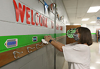 Pam Henbest,a first grade teacher at Asbell Elementary School, hangs name tags on coat and back pack hooks Wednesday, August 19, 2020, for her incoming students in her classroom at the school in Fayetteville. School starts on August 24 in a continuation of the pandemic that closed in-class learning last spring. This year, schools have been told to be ready for both virtual and in-class and be ready to switch up proportions of each if necessary. Check out nwaonline.com/200823Daily/ and nwadg.com/photos for a photo gallery.<br /> (NWA Democrat-Gazette/David Gottschalk)