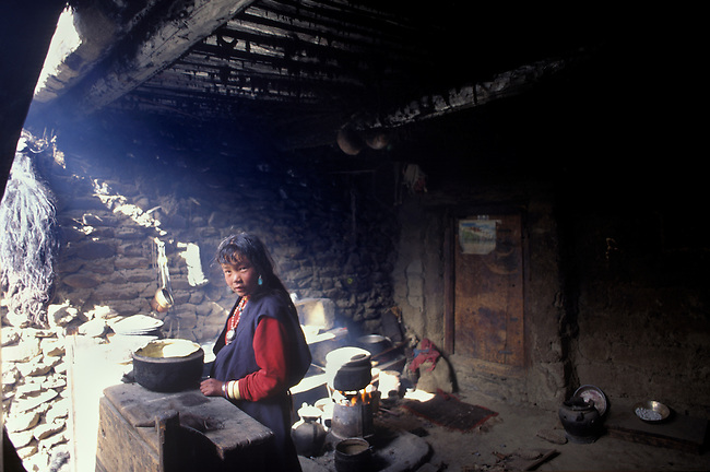 A DOLPO WOMAN cooks in the KITCHEN of SHIP CHOK MONASTERY in the DO TARAP VALLEY - DOLPO, NEPAL