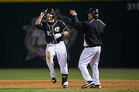 Jason Coats (17) of the Charlotte Knights gets a shove from first base coach Tyler Saladino (8) after hitting a walk-off single to defeat the Toledo Mud Hens at BB&T BallPark on April 27, 2015 in Charlotte, North Carolina.  The Knights defeated the Mud Hens 7-6 in 10 innings.   (Brian Westerholt/Four Seam Images)