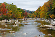 Autumn foliage along the East Branch of the Pemigewasset River in Lincoln, New Hampshire on a cloudy autumn day. This location, near where Clear Brook drains into the East Branch of the Pemi, is where the No. 2 Dam (from the Lincoln Mill era) was located. Little of the dam remains today.
