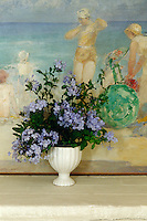 An earthenware vase full of blue plumbago is arranged in front of an oil painting by the Russian artist, Schmaroff in the dining room