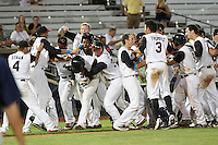 Quad Cities River Bandits Randy Cesar (39) is mobbed by teammates, including Myles Straw (4), Christian Correa (9), Kristian Trompiz (3), Kyle Tucker (19), after a walk off hit during a game against the Bowling Green Hot Rods on July 24, 2016 at Modern Woodmen Park in Davenport, Iowa.  Quad Cities defeated Bowling Green 6-5.  (Mike Janes/Four Seam Images)