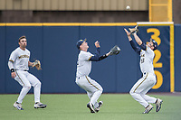 Michigan Wolverines first baseman Jake Bivens (18) catches a pop up as teammates Jimmy Kerr (15) and Jonathan Engelmann (2) look on against the Michigan State Spartans on May 19, 2017 at Ray Fisher Stadium in Ann Arbor, Michigan. Michigan defeated Michigan State 11-6. (Andrew Woolley/Four Seam Images)