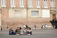 Turisti seduti in Piazza Maggiore a Bologna.<br /> Tourists sit on the ground in piazza Maggiore, Bologna.<br /> UPDATE IMAGES PRESS/Riccardo De Luca