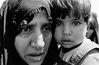 """Iraq. Baghdad. A mother holds her young daughter in her arms. The """" Committee for free prisoners"""" establishes various lists of the people which were executed by Saddam Hussein regime. Families come everyday to read the lists and collect informations on their loved parents, hoping to know their whereabouts. © 2003 Didier Ruef"""