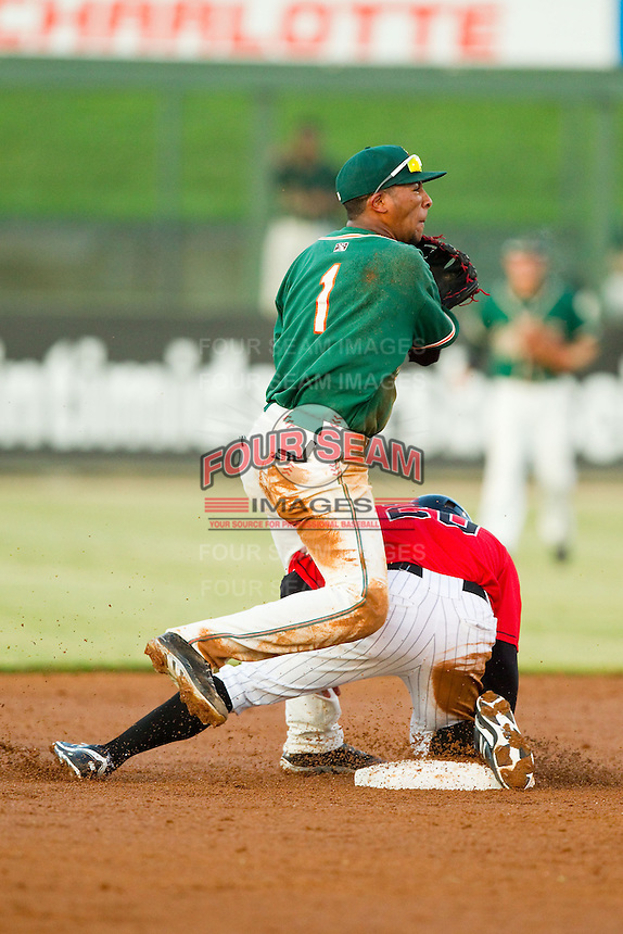Greensboro Grasshoppers second baseman Rehiner Cordova (1) attempts to turn a double play as Jacob May (20) of the Kannapolis Intimidators slides into second base at CMC-Northeast Stadium on July 15, 2013 in Kannapolis, North Carolina.  The Intimidators defeated the Grasshoppers 4-0.   (Brian Westerholt/Four Seam Images)