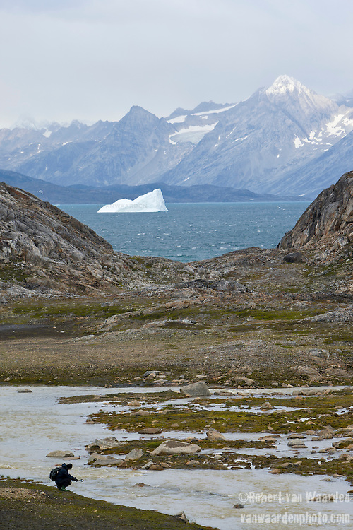 A woman records the sound of a river in Eastern Greenland. In the background, an iceberg and the mountainous landscape of Greenland.