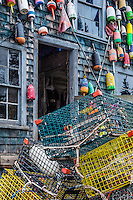 Colorful buoys adorn a rustic coastal shack, Bernard, Mt Desert Island, Maine, USA