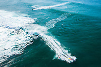 An aerial view of waves rushing towards the North Shore of O'ahu, with jet skiers towing surfers into the big waves.