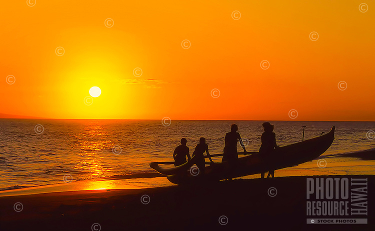 A crew of women bring in an outrigger canoe at sunset on Ka'anapali Beach, Maui.