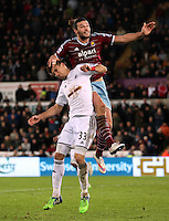 Pictured: Andy Carroll of West Ham jumps over Federico Fernandez of Swansea Saturday 10 January 2015<br /> Re: Barclays Premier League, Swansea City FC v West Ham United at the Liberty Stadium, south Wales, UK