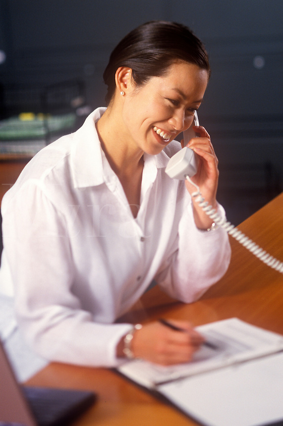Pleasant smiling woman talks on office phone.