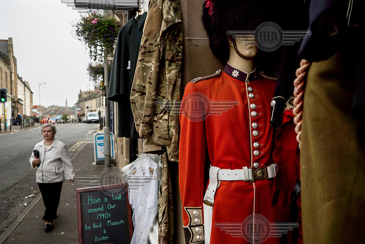 A woman walks past a military shop with a mannequin wearing the uniform of the Coldstream Guards in the Scottish border town of Coldstream.