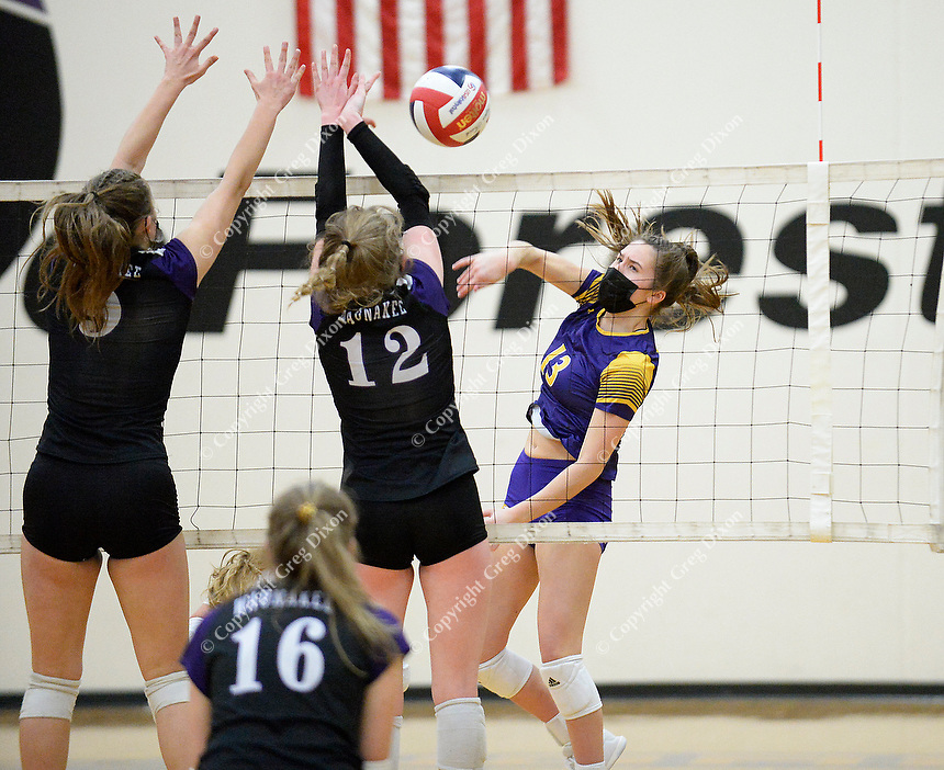 DeForest's Reese Yocum (13) hits past Waunakee defenders Mariah Best (12) and Allie Mack (5), as DeForest tops Waunakee 3 sets to 1 in Wisconsin WIAA girls high school volleyball regional finals on Saturday, Apr. 10, 2021 at DeForest High School