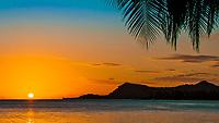 Orange sunset with small clouds and a palm tree leaf over Bora Bora island, a romantic honeymoon destination, near Tahiti, Polynesia, Pacific Ocean