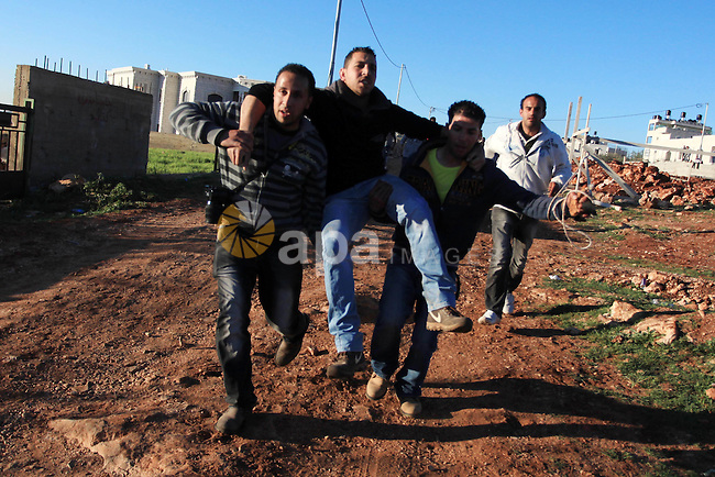 Palestinian men carry an injured comrade during clashes with Israeli security forces in the West Bank village of Silwad, north of Ramallah, on March 21, 2014 following a protest of Palestinians against the expansion of the nearby Israeli settlement of Ofra. Photo by Issam Rimawi