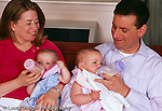8 month old fraternal twin girls with mother and father fed bottles    horizontal