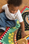 17 month old toddler boy playing with shape sorter putting shape into shape sorter