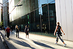 People walking, sunset, silhouette, along a Glass-building at the River Thames, near Tooley Street and Potter`s Fields, London, England, United Kingdom, Great Britain