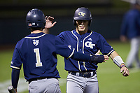 Kevin Parada (4) of the Georgia Tech Yellow Jackets is greeted at home plate by teammate Tres Gonzalez (1) after scoring a run against the Virginia Tech Hokies at English Field on April 16, 2021 in Blacksburg, Virginia. (Brian Westerholt/Four Seam Images)